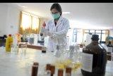 Seorang dosen membuat Hand Sanitizer atau cairan pembersih tangan dari bahan minuman Arak Bali di Universitas Udayana, Badung, Bali, Kamis (2/4/2020). Polda Bali bekerja sama dengan Universitas Udayana melakukan pengolahan Arak Bali yang diperoleh dari masyarakat untuk dijadikan Hand Sanitizer yang akan dibagikan secara gratis kepada masyarakat untuk mengantisipasi penyebaran COVID-19. ANTARA FOTO/Fikri Yusuf/nym.