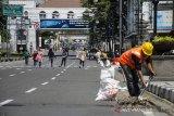 Warga berjalan di Kawasan Asia Afrika yang ditutup untuk kendaraan di Bandung, Jawa Barat, Jumat (3/4/2020). Sejumlah ruas Jalan Protokol di Kota Bandung ditutup sementara pelaksanaan gerakan social distancing dan pengurangan titik kumpul warga guna pencegahan dan pengurangan resiko penyebaran virus COVID-19. ANTARA JABAR/Novrian Arbi/agr
