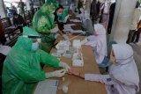 Tim medis Dinas Kesehatan Kabupaten Tabanan melakukan test cepat terhadap sejumlah santri yang baru tiba di Terminal Pesiapan, Tabanan, Bali, Jumat (3/4/2020). Ratusan santri yang dipulangkan dari pondok pesantren di Jawa Timur tersebut didata dan diperiksa oleh tim medis serta menjalani isolasi mandiri selama 14 hari sebagai upaya pencegahan penyebaran COVID-19 atau Virus Corona. ANTARA FOTO/Nyoman Hendra Wibowo/nym