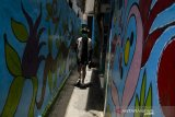 Warga melintasi sejumlah lukisan pada tembok kampung Mural Bagusrangin, Bandung, Jawa Barat, Sabtu (4/4/2020). Pemukiman dengan mayoritas gang sempit di kawasan tersebut dilukis guna  memperindah dan terlihat bersih sehingga mampu menjadi alternatif wisata bagi masyarakat Kota Bandung. ANTARA JABAR/Novrian Arbi/agr
