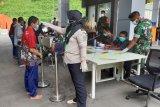 Petugas Kantor Kesehatan Pelabuhan Entikong mengukur suhu tubuh WNI yang baru datang dari Sarawak Malaysia di pintu kedatangan Pos Lintas Batas Negara (PLBN) Entikong, Kabupaten Sanggau, Kalimantan Barat, Jumat (3/4/2020). Kantor Kesehatan Pelabuhan Entikong bersama Pamtas dari Yonif Raider 641/Bru memperketat pemeriksaan kesehatan serta penyemprotan disinfektan terhadap WNI yang tiba dari Sarawak Malaysia melalui PLBN Entikong guna mencegah penyebaran virus COVID-19. ANTARA FOTO/Agus Alfian/jhw/aww.