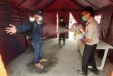 Petugas Kantor Kesehatan Pelabuhan Entikong menyemprot disinfektan ke WNI yang baru datang dari Sarawak Malaysia di pintu kedatangan Pos Lintas Batas Negara Entikong, Kabupaten Sanggau, Kalimantan Barat, Jumat (3/4/2020). Kantor Kesehatan Pelabuhan Entikong bersama Pamtas dari Yonif Raider 641/Bru memperketat pemeriksaan kesehatan serta penyemprotan disinfektan terhadap WNI yang tiba dari Sarawak Malaysia melalui PLBN Entikong guna mencegah penyebaran virus COVID-19. ANTARA FOTO/Agus Alfian/jhw/aww.