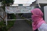 Warga melintas di depan pintu masuk Kampung Pucang Sewu yang melakukan karantina wilayah, Surabaya, Jawa Timur, Minggu (5/4/2020). Karantina wilayah tersebut dilakukan oleh warga di kampung itu guna mencegah penyebaran Virus Corona (COVID-19). Antara Jatim/Zabur Karuru