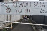 KARANTINA WILAYAH DI SURABAYA. Warga melintas di depan pintu masuk Kampung Pucang Sewu yang melakukan karantina wilayah, Surabaya, Jawa Timur, Minggu (5/4/2020). Karantina wilayah tersebut dilakukan oleh warga di kampung itu guna mencegah penyebaran Virus Corona (COVID-19). Antara Jatim/Zabur Karuru