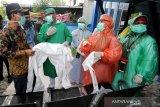 Ketua DPRK Banda Aceh Farid Nyak Umar (kiri) berbincang dengan petugas medis puskesmas Kuta Alam yang memakai jas hujan plastik sebagai Alat Pelindung Diri (APD) untuk melayani pasien di Banda Aceh, Aceh, Senin (6/4/2020). Petugas medis ditingkat puskesmas terpaksa menggunakan jas hujan karena keterbatasan APD yang sesuai standar guna mencegah penularan virus Corona (COVID-19). Antara Aceh/Irwansyah Putra.
