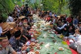 Sejumlah warga menyantap makanan bersama saat Nyadran Perdamaian di Krecek, Getas, Kaloran, Temanggung, Jawa Tengah, Jumat (13/3/2020). Tradisi Nyadran lintas agama Islam, Kristen, Katholik, Budha dan penganut kepercayaan tersebut telah berlangsung sejak puluhan tahun silam yang bertujuan untuk mendoakan arwah leluhur sekaligus sebagai wujud kerukunan antar pemeluk agama. FOTO ANTARA/Anis Efizudin/pd.