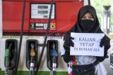 Petugas SPBU Lilis Setiawati (24) menunjukan kertas berisi pesan untuk tetap di rumah di tempat kerjanya di Jakarta, Sabtu (4/4/2020). Sejumlah warga masih melakukan aktivitas kerja di luar rumah seperti biasanya meski di saat pandemi COVID-19 agar tetap memberikan pelayanan kepada warga. ANTARA FOTO/Hafidz Mubarak A/hp.
