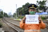 Petugas penjaga palang pintu kereta api Dedi (44) menunjukan pesan untuk tetap di rumah dari tempat kerjanya di Jakarta, Sabtu (4/4/2020). Sejumlah warga masih melakukan aktivitas kerja di luar rumah seperti biasanya meski di saat pandemi COVID-19 agar tetap memberikan pelayanan kepada warga. ANTARA FOTO/Hafidz Mubarak A/hp.