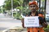 Petugas Penanganan Prasarana dan Sarana Umum (PPSU) Sudjarot (42) menyampaikan pesan untuk tetap di rumah dari tempat ia bekerja di Jakarta, Sabtu (4/4/2020). Sejumlah warga masih melakukan aktivitas kerja di luar rumah seperti biasanya meski di saat pandemi COVID-19 agar tetap memberikan pelayanan kepada warga. ANTARA FOTO/Hafidz Mubarak A/hp.