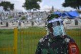 Anggota TNI melakukan pengamanan saat warga melakukan aksi menutup jalan menuju ke pemakaman Macanda di Kecamatan Somba Opu, Kabupaten Gowa, Sulawesi Selatan, Kamis (2/4/2020). Penutupan akses jalan yang dilakukan sejumlah warga yang bermukim disekitar pemakaman Macanda tersebut sebagai bentuk penolakan terhadap pemakaman jenazah pengidap COVID-19. ANTARA FOTO/Abriawan Abhe/foc.