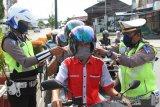 Sejumlah Polisi Satuan Lalu Lintas Polres Aceh Barat membagikan masker ke pengendara sepeda motor di salah satu persimpangan Kota Meulaboh, Aceh Barat, Aceh, Selasa (7/4/2020). Satuan Lalu Lintas Polres Aceh Barat membagikan puluhan masker gratis kepada pengendara sepeda motor yang tertib berlalu lintas menyusul himbauan Organisasi Kesehatan Dunia (WHO) dan Pemerintah agar masyarakat menggunakan masker saat berada di luar rumah untuk mengurangi resiko penyebaran dan penularan COVID-19. Antara Aceh/Syifa Yulinnas.