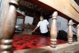 Perangkat desa membersihkan rumah yang disiapkan sebagai ruang isolasi mandiri di Desa Kemiren, Banyuwangi, Jawa Timur, Rabu (8/4/2020). Pemerintah daerah setempat, mengintruksikan agar setiap desa menyediakan tempat isolasi mandiri untuk warga yang berstatus Orang Dalam Pemantauan (ODP) atau perantau dari wilayah zona merah, sebagai upaya pencegahan penyebaran COVID-19. Antara Jatim/Budi Candra Setya/zk.