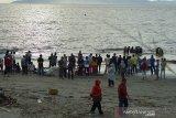 Sejumlah pengunjung menyaksikan nelayan menangkap ikan menggunakan alat tangkat pukat pantai di Desa Kampung Jawa, Banda Aceh, Aceh, Rabu (8/4/2020). Pemerintah di daerah itu mengimbau agar masyarakat untuk menghindari keramaian, menjaga jara fisik (physical distancing) dan menggunakan masker untuk mencegah penyebaran Corona Virus (COVID-19). Antara Aceh/Ampelsa
