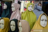 Pedagang jilbab menggunakan masker saat berjualan di Pasar Cicadas, Bandung, Jawa Barat, Rabu (8/4/2020). Pemerintah mewajibkan masyarakat untuk menggunakan masker saat beraktivitas di luar rumah sebagai antisipasi penyebaran dan peningkatan kesadaran bagi masyarakat akan bahaya pandemi COVID-19. ANTARA JABAR/Novrian Arbi/agr
