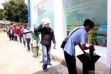 Pemohon pembuatan Surat Izin Mengemudi (SIM) mengantre untuk mencuci tangan di Satpas Banyuwangi, Jawa Timur, Rabu (8/4/2020). Satpas Banyuwangi kembali membuka pelayanan pembuatan dan perpanjangan SIM dengan Standar Operasional prosedur (SOP) seperti menggunakan masker, penyediaan bilik disinfektan, jaga jarak serta menggelar senam dibawah terik matahari setelah sepekan terahir ditutup akibat wabah COVID-19. Antara Jatim/Budi Candra Setya/zk.