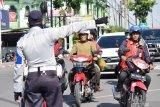 Petugas menertibkan pengendara yang tidak mengenakan masker  untuk tidak memasuki kawasan di Kota Madiun, Jawa Timur, Rabu (8/4/2020). Pemkot Madiun mulai menerapkan wajib mengenakan masker bagi warga di ruang publik dan mulai dilakukan penertiban di sejumlah lokasi guna pencegahan penyeberan COVID-19. Antara Jatim/Siswowidodo/zk.