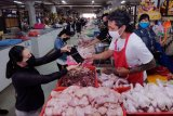 Petugas Koordinator Kegiatan Kesejahteraan Sosial (KKKS) Kota Denpasar membagikan masker gratis kepada pedagang di Pasar Badung, Denpasar, Bali, Rabu (8/4/2020). Kegiatan tersebut merupakan program gerakan 10 ribu masker yang diberikan secara gratis kepada pedagang di pasar tradisional, petugas kebersihan jalan, petugas parkir serta petugas disinfektan untuk mencegah penyebaran COVID-19 atau Virus Corona. ANTARA FOTO/Nyoman Hendra Wibowo/nym.