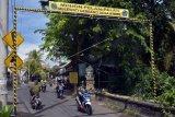 Pengendara sepeda motor melintasi gerbang penyemprotan disinfektan yang dipasang di jalan Desa Batubulan, Gianyar, Bali, Rabu (8/4/2020). Pemasangan gerbang penyemprotan disinfektan yang disebut dengan gerbang desa steril itu merupakan upaya masyarakat setempat untuk mencegah penyebaran COVID-19 atau Virus Corona. ANTARA FOTO/Nyoman Hendra Wibowo/nym