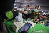 Pedagang memberikan pesanan sayur-mayur kepada pengemudi daring di pasar Kosambi, Bandung, Jawa Barat, Jumat (10/4/2020). Layanan belanja online dan siap antar tersebut bertujuan untuk membatasi lalu lalang orang di pasar dan juga sebagai upaya pencegahan penyebaran COVID-19. ANTARA JABAR/M Agung Rajasa/agr