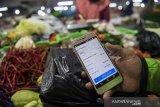 Pengemudi daring menunjukan pesanan belanja online di pasar Kosambi, Bandung, Jawa Barat, Jumat (10/4/2020). Layanan belanja online dan siap antar tersebut bertujuan untuk membatasi lalu lalang orang di pasar dan juga sebagai upaya pencegahan penyebaran COVID-19. ANTARA JABAR/M Agung Rajasa/agr