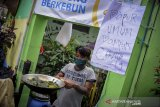 Seorang warga menyiapkan makanan untuk diberikan secara gratis kepada warga terdampak COVID-19 di Lio Genteng, Astana Anyar, Bandung, Jawa Barat, Jumat (10/4/2020). Pembagian makan gratis hasil swadaya masyarakat itu ditujukan sebagai bentuk kepedulian terhadap warga terdampak COVID-19 yang kehilangan mata pencahariannya di wilayah tersebut. ANTARA JABAR/Raisan Al Farisi/agr