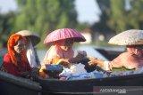 Pedagang melakukan transaksi di atas perahu di pasar terapung Lok Baintan, Desa Lok Baintan, Kabupaten Banjar, Kalimantan Selatan, Jumat (10/4/2020). Menurut pedagang setempat, pembeli maupun wisatawan yang berkunjung ke pasar tersebut mengalami penurunan sejak merebaknya wabah COVID-19. Foto Antaranews Kalsel/Bayu Pratama S.