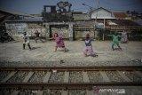 Warga berjemur sekaligus berolahraga di samping rel kereta api di Andir, Bandung, Jawa Barat, Rabu (15/4/2020). Saat pandemi COVID-19 yang tengah mewabah di Indonesia, warga yang tinggal di bantaran rel kereta api tersebut memanfaatkan lengangnya perjalan kereta api untuk berjemur dan berolahraga agar menjaga imunitas tubuh. ANTARA JABAR/Raisan Al Farisi/agr