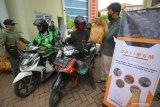 Sivitas akademika Universitas Muhammadiyah Surabaya (UMS) membagikan paket sembako dan masker kepada pengemudi ojek daring di Surabaya, Jawa Timur, Jumat (17/4/2020). Kegiatan bertajuk Optimisme UMS (Optimum) tersebut bertujuan untuk menyebar optimisme dan wujud saling tolong menolong kepada warga yang terdampak langsung pandemi COVID-19. Antara Jatim/Moch Asim/zk.