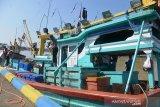 Personil Dit Pol Air Polda Aceh menyemprotkan cairan disinfektan pada kapal nelayan seusai melaut di pos pemantauan dermaga Pelabauhan Desa Lampulo, Banda Aceh, Aceh, Senin (20/4/2020). Setiap kapal nelayan yang berangkat dan pulang melaut mendapat penyemprotan disinfektan untuk mencegah penyeberan Corona Virus (COVID-19). Antara Aceh/Ampelsa.