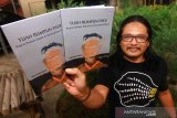 Jurnalis Pontianak Aries Munandar memperlihatkan buku hasil karyanya yang berjudul Tuah Rumpun Padi di Pontianak, Kalimantan Barat, Senin (20/4/2020). Buku Tuah Rumpun Padi yang berisi kumpulan tulisan karangan khas (feature) dari tahun 2010 tersebut bercerita tentang ragam kehidupan dan kebudayaan masyarakat adat Dayak di Kalimantan Barat. ANTARA FOTO/Jessica Helena Wuysang