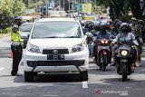 Petugas gabungan mengatur lalu lintas kendaraan dari luar kota saat penerapan Pembatasan Sosial Berskala Besar (PSBB) di Pasteur, Bandung, Jawa Barat, Rabu (22/4/2020). Pemeriksaan tersebut dilakukan untuk mengingatkan masyarakat agar menerapkan PSBB selama 14 hari dalam rangka percepatan penanganan COVID-19. ANTARA JABAR/M Agung Rajasa/agr