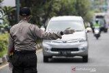 Polisi mengarahkan kendaraan roda empat untuk menjalani pemeriksaan saat penerapan Pembatasan Sosial Berskala Besar (PSBB) di Pasteur, Bandung, Jawa Barat, Rabu (22/4/2020). Pemeriksaan tersebut dilakukan untuk mengingatkan masyarakat agar menerapkan PSBB selama 14 hari dalam rangka percepatan penanganan COVID-19. ANTARA JABAR/M Agung Rajasa/agr