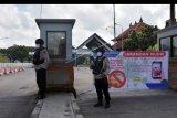 Anggota Brimob Polda Bali berjaga di area pintu masuk Terminal Mengwi, Badung, Bali, Senin (27/4/2020). Terminal terbesar di pulau Bali tersebut tidak beroperasi hingga 31 Mei 2020 dan diperketat pengamanannya menyusul larangan mudik untuk mengurangi risiko penularan COVID-19. ANTARA FOTO/Nyoman Hendra Wibowo/nym.