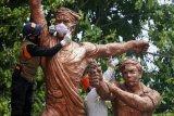 Memasang masker di patung Monumen Djoeang 45
