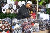 Pedagang musiman menata songkok jualannya di Sukun, Malang, Jawa Timur, Selasa (28/4/2020). Pedagang musiman setempat, mengaku penjualan pernik Ramadhan terutama songkok menurun 70 persen dibanding tahun lalu seiring adanya penerapan pembatasan jarak sosial serta himbauan tarawih di rumah dalam rangka pencegahan penyebaran COVID-19. ANTARA FOTO/Ari Bowo Sucipto/foc.