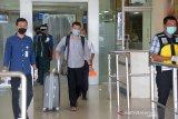 Seorang mahasiswa asal Aceh, Munjir (tengah) didampinbgi petugas keluar melalui pintu domestik saat tiba di Bandara Internasional Sultan Iskandar Muda, Blang Bintang, Kabupaten ,Aceh Besar, Aceh (29/4/2020). Mahasiswa asal Aceh yang kuliah di salah universitas Mesir itu dinyatakan negatif Covid-19 setelah menjalani pemeriksaan oleh tim dokter kesehatan di Bandara Internasional Sultan Iskandar Muda, Aceh. Antara Aceh/Ampelsa.
