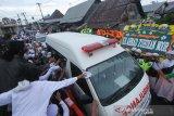 Warga menyaksikan iring-iringan mobil jenazah KH Ahmad Zuhdiannoor saat melintas di jalan menuju kediaman di Banjarmasin, Kalimantan Selatan, Sabtu (2/5/2020). Ulama karismatik KH Ahmad Zuhdiannoor atau yang akrab disapa Guru Zuhdi wafat pada usia 47 tahun pada hari Sabtu (2/5/2020) saat dalam penanganan medis di Rumah Sakit Medistra Jakarta. Foto Antaranews Kalsel/Bayu Pratama S.