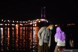 KAWASAN JEMBATAN SURAMADU. Warga saling bercengkrama di sisi timur Jembatan Suramadu di Surabaya, Jawa Timur, Sabtu (18/4/2020). Akibat pendemi Virus Corona (COVID-19), suasana di kawasan itu sepi pengunjung. Antara Jatim/Zabur Karuru