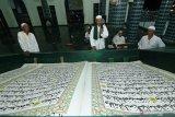 TADARUS AL QURAN RAKSASA. Umat muslim bertadarus membaca Al Quran raksasa di Masjid Baiturrahman, Banyuwangi, Jawa Timur, Senin (27/4/2020). Al Quran raksasa ditulis tangan oleh H Abdul Karim memiliki ukuran halaman 142 x 210 centimeter tersebut, mulai ditulis pada 1 Februari 2010 dan selesai pada 26 Agustus 2010 untuk dibaca setiap bulan Ramadan di Masjid Baiturrahman Banyuwangi Antara Jatim/Budi Candra Setya/zk