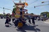 Sejumlah warga mengiringi arak-arakan Wadah atau keranda hias yang berisi jenazah tokoh Puri Kawan Kesiman dalam prosesi upacara Ngaben di Denpasar, Bali, Selasa (5/5/2020). Upacara Ngaben bagi tokoh masyarakat yang biasanya melibatkan ratusan hingga ribuan warga tersebut, saat ini hanya diizinkan diikuti orang dalam jumlah sangat terbatas untuk mengurangi risiko penyebaran wabah COVID-19. ANTARA FOTO/Nyoman Hendra Wibowo/nym.