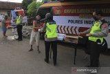 Polisi membagikan makanan untuk berbuka puasa kepada warga di kelurahan Bojongsari, Indramayu, Jawa Barat, Rabu (6/5/2020). Pembagian paket makanan berbuka puasa dari dapur umum Polres Indramayu itu sebagai bentuk kepedulian dan meringankan beban masyakarat di tengah pandemi COVID-19. ANTARA JABAR/Dedhez Anggara/agr