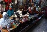 Pedagang batik menunggu pembeli di Pasar 17 Agustus, Pamekasan, Jawa Timur, Kamis (7/5/2020). Hingga pekan ke dua bulan puasa tahun ini penjualan batik Pamekasan sepi pembeli, karena pelanggan, seperti perusahaan dan perkantoran dari berbagai daerah yang biasa membeli dalam jumlah banyak untuk kebutuhan THR itu, terhenti akibat Pandemi COVID-19. Antara Jatim/Saiful Bahri/zk