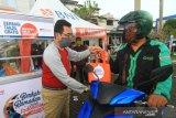 Head Of Network and Service BNI area Kalbar Kartiko S Wijayanto (kiri)  membagikan makanan dan minuman berbuka puasa (takjil) untuk pengguna jalan yang melintasi BNI Kantor Cabang Pontianak di Jalan Tanjungpura, Pontianak, Kalimantan Barat, Sabtu (9/5/2020). Kartiko S Wijayanto menyatakan bahwa kegiatan BNI berbagi takjil gratis sebanyak 600 paket untuk masyarakat tersebut merupakan bagian dari rangkaian Program Berkah Ramadan untuk Indonesia. ANTARA FOTO/Jessica Helena Wuysang