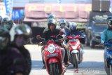 Seorang pengendara motor melintas pos Pembatasan Sosial Bersakala Besar (PSBB) tanpa menggunakan masker di jalan Ahmad Yani Banjarmasin, Kalimantan Selatan, Minggu (10/5/2020). Seorang pengendara motor melintas pos Pembatasan Sosial Bersakala Besar (PSBB) tanpa menggunakan masker di jalan Ahmad Yani Banjarmasin, Kalimantan Selatan, Minggu (10/5/2020). Meskipun Kota Banjarmasin telah melanjutkan Pembatasan Sosial Berskala Besar (PSBB) tahap kedua masih banyak warga yang mengabaikan aturan berkendara seperti tidak menggunakan masker. Foto Antaranews Kalsel/Bayu Pratama S.