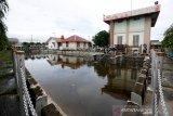 Petugas membersihkan sampah plastik yang menumpuk di kolam penampungan stasiun rumah pompa Punge, Banda Aceh, Aceh, Minggu (10/5/2020). Sampah plastik yang menyumbat saluran pembuangan menjadi salah satu kendala yang dihadapi sembilan stasiun rumah pompa bantuan Multi Donor Fund (MDF) di Kota Banda Aceh dalam mengantisipasi banjir genangan yang sering terjadi pada musim penghujan. Antara Aceh/Irwansyah Putra.