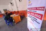 Petugas melakukan pendataan kepada warga yang menerima Bantuan Sosial Tunai (BTS) di Kantor Pos Banjarmasin, Kalimantan Selatan, Senin (11/5/2020). Pemerintah setempat menyalurkan BST senilai Rp600 ribu per Keluarga Penerima Manfaat (KPM) selama tiga bulan ke depan dari Kementerian Sosial kepada 15.879 KPM di Kota Banjarmasin yang terdampak wabah COVID-19. Foto Antaranews Kalsel/Bayu Pratama S