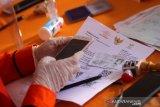 Petugas melakukan pendataan kepada warga yang menerima Bantuan Sosial Tunai (BTS) di Kantor Pos Banjarmasin, Kalimantan Selatan, Senin (11/5/2020). Pemerintah setempat menyalurkan BST senilai Rp600 ribu per Keluarga Penerima Manfaat (KPM) selama tiga bulan ke depan dari Kementerian Sosial kepada 15.879 KPM di Kota Banjarmasin yang terdampak wabah COVID-19. Foto Antaranews Kalsel/Bayu Pratama S.