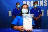 Kepala Seksi Pengawasan Tahanan dan Barang Bukti BNNP Kalbar Anida Sari (tengah) memperlihatkan barang bukti sabu saat rilis kasus penangkapan tiga kurir sabu lintas Kalimantan di Kantor BNNP Kalbar di Pontianak, Kalimantan Barat, Senin (11/5/2020). BNNP Kalbar membekuk tiga kurir narkoba berinisial Mus (27), DI (43) dan PH (35) yang sedang bertransaksi membeli satu kilogram sabu serta lima butir ekstasi di Desa Jawa Tengah, Kabupaten Kubu Raya, Kalbar yang selanjutnya akan diantarkan melalui jalan darat ke pemesannya berinisial A (DPO) di Palangka Raya, Kalimantan Tengah. ANTARA FOTO/Jessica Helena Wuysang
