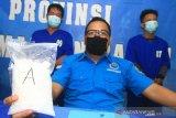 Kepala Seksi Penyidikan Bidang Pemberantasan BNN Provinsi Kalbar Stevanny Valentino (tengah) memperlihatkan barang bukti sabu saat rilis kasus penangkapan tiga kurir sabu lintas Kalimantan di Kantor BNNP Kalbar di Pontianak, Kalimantan Barat, Senin (11/5/2020). BNNP Kalbar membekuk tiga kurir narkoba berinisial Mus (27), DI (43) dan PH (35) yang sedang bertransaksi membeli satu kilogram sabu serta lima butir ekstasi di Desa Jawa Tengah, Kabupaten Kubu Raya, Kalbar yang selanjutnya akan diantarkan melalui jalan darat ke pemesannya berinisial A (DPO) di Palangka Raya, Kalimantan Tengah. ANTARA FOTO/Jessica Helena Wuysang