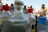 Wakapolres Blitar Kompol Himawan memecahkan botol minuman keras lokal hasil operasi gabungan Satpol PP dan Polres Blitar saat pemusnahan barang bukti di halaman Pendopo Sasana Adhi Praja, Blitar, Jawa Timur, Selasa (12/5/2020). Pemusnahan tersebut bertujuan untuk menekan peredaran minuman keras, serta menjaga kesucian bulan ramadhan, sekaligus menekan angka kriminalitas selama Ramadhan hingga jelang Idul Fitri. Antara Jatim/Irfan Anshori/zk.